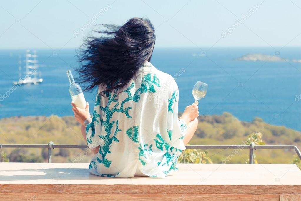 Beauty young woman with glass of wine face to the sea