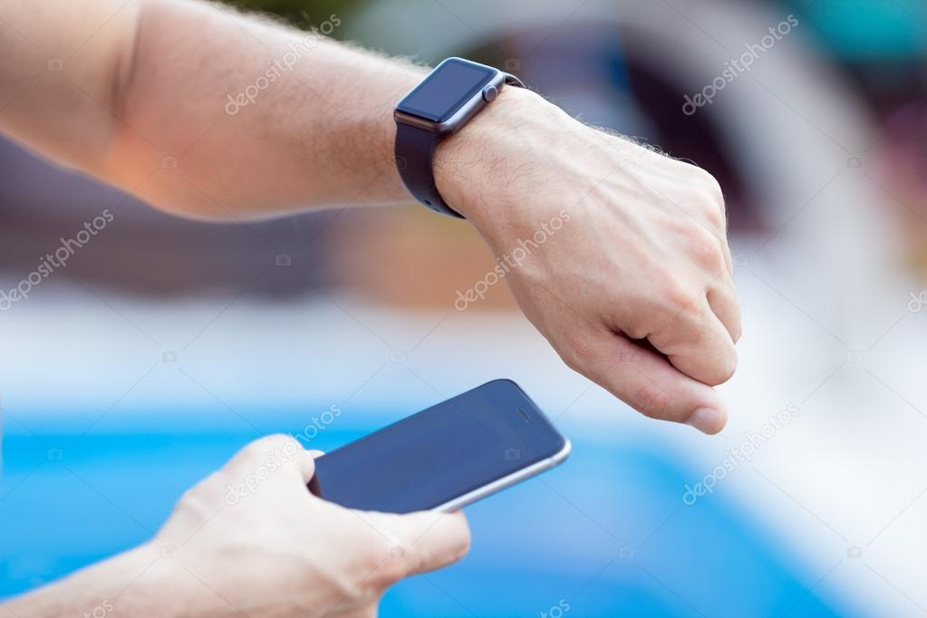 Male hands with black smartwatch on a background of water pool