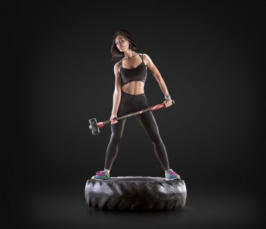 Athletic young woman doing a fitness workout with hammer and tire on black studio background
