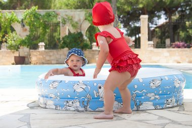 A happy young child is playing outside in a baby swimming pool