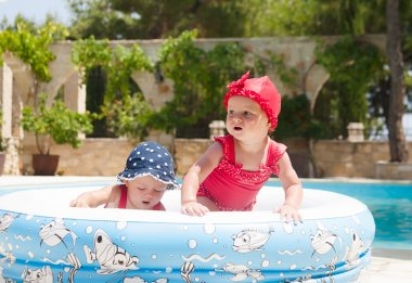 A happy young children is playing outside in a baby swimming pool