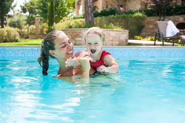 Happy young active mother and  curly little baby having fun in a swimming pool
