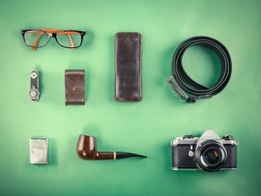 Set of Retro hipster mock up. Laptop, old camera, tablet and smoke pipe on green background. Filtered image
