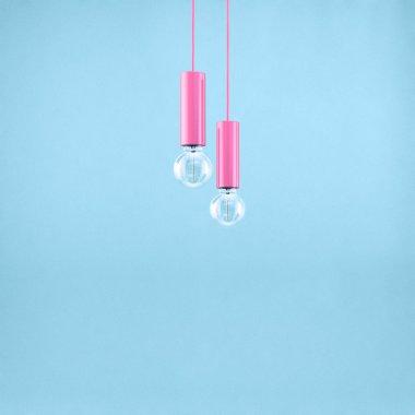 Decorative antique edison style filament light bulb on light blue background. Filtered image