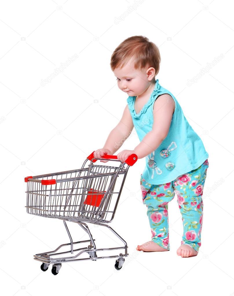 648c92b2e765 Baby girl pushing shopping trolley — Stock Photo © iagodina  69325019