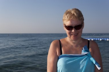 Middle-aged woman in a pareo and sunglasses