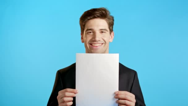 Portrét mladého pohledného podnikatele v obleku drží bílý vertikální a4 papír izolované na modrém pozadí studia.Copy prostor.