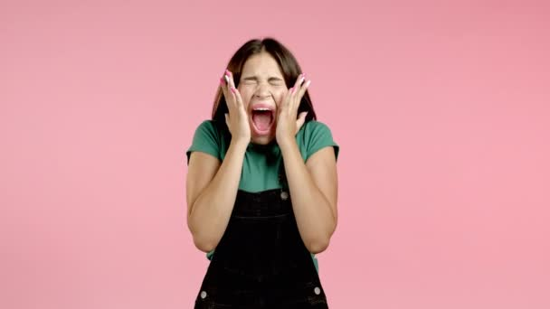 Frightened and screaming woman shocked isolated over pink background. Stressed and depressed pretty girl because of bad news.