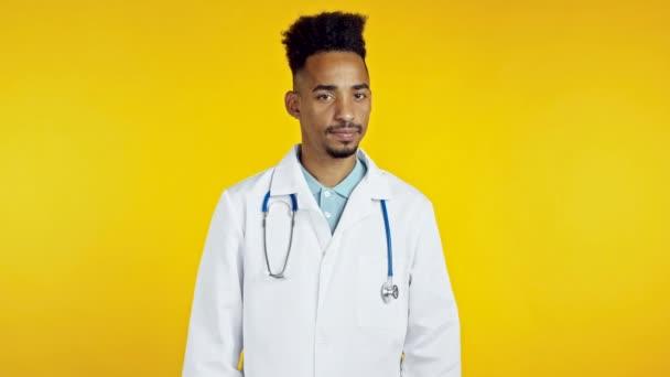 Portrét seriózního afrického lékaře v lékařském bílém plášti s odmítavým gestem hlavy a nesouhlasným znamením. Popírám, nesouhlasím. Doc man izolované na žlutém pozadí.