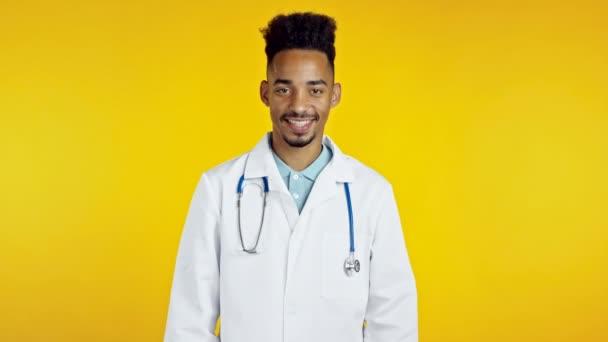 Portrét spokojeného doktora v profesionálním lékařském kabátě s nápisem ano po hlavě. Smíšený rasista to dovolí, pochvaluje si to. Doc man izolované na žlutém pozadí.