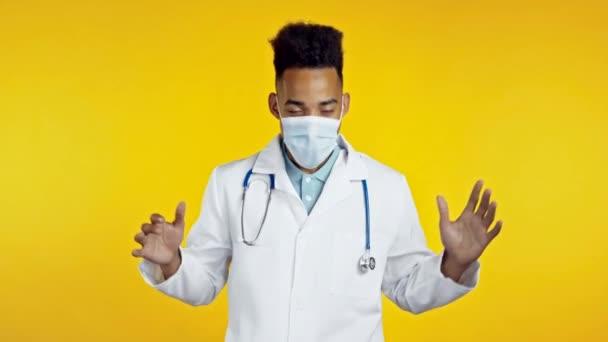 Afrikanisch-amerikanischer Arzt witzig tanzen, Erfolg und Glück bei der Arbeit. Junger gutaussehender Doc-Mann in medizinischem weißen Mantel ist isoliert auf gelbem Studiohintergrund.