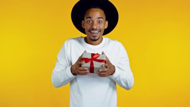 Mladý afro muž, který drží dárkovou krabici s lukem, se diví, co je uvnitř. Žluté pozadí zdi. Afričan hipster chlap v klobouku s úsměvem, je šťastný, že dostat dárek.