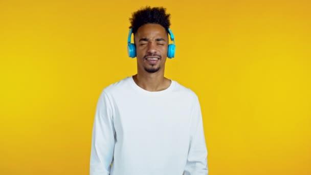 Handsome african man having fun, dancing head with blue headphones in yellow studio. Music, dance, radio concept, slow motion