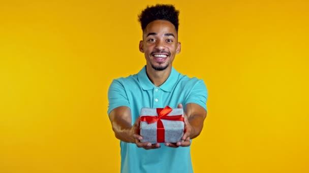 Nadšený africký muž drží dárkovou krabici a dává ji rukou k fotoaparátu na žlutém pozadí stěny. Chlápek, co se usmívá, je šťastný s přítomností. Studio portrét