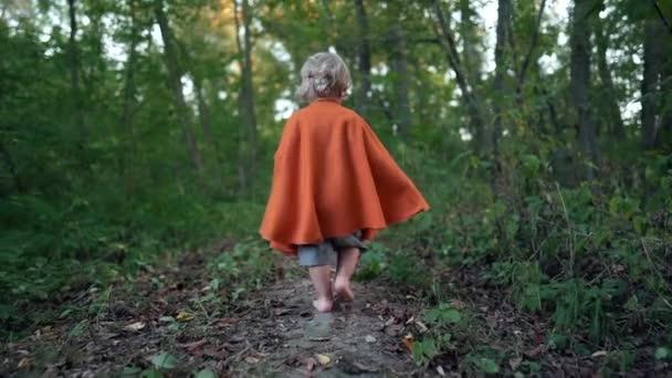 Kis totyogó fiú jelmezes törpe vagy hobbit hosszú köpenyben mezítláb sétál a zöld erdőben. Halloween, gyerekkoncepció. Csodálatos tündérmese karakter. Lassú mozgás..