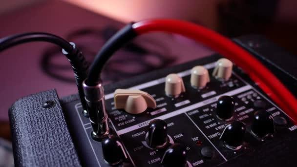 Mans ruka odstraňuje kabel jack z kytarového zesilovače