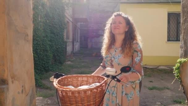 Porträt einer jungen lächelnden Frau mit lockigem rotem Haar, die mit einem Oldtimer-Fahrrad im alten europäischen Hof steht. Zeitlupe.