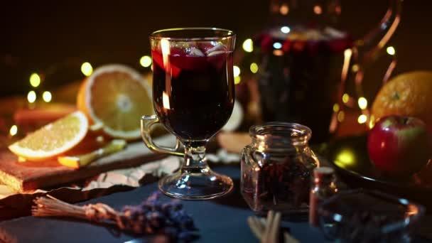Atemberaubende Aussicht auf Glühwein mit Honig, Früchten und Gewürzen. Duftende Atmosphäre von Weihnachten Winterurlaub. Glas mit Zimt und Orange auf dem Tisch mit leuchtenden Girlanden. 4k