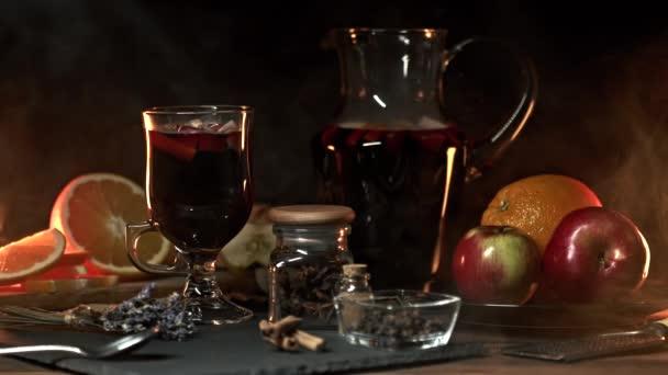 Stillleben - Glühwein, heißer Rotwein mit Gewürzen im Glas zwischen den Früchten. Duftendes gemütliches Weihnachtsfest, duftendes Punschkonzept.