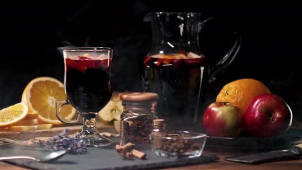 Atemberaubende Aussicht auf Glühwein mit Honig, Früchten und Gewürzen. Duftende Atmosphäre von Weihnachten Winterurlaub. Glas mit Zimt und Orange auf dem Tisch. 4k