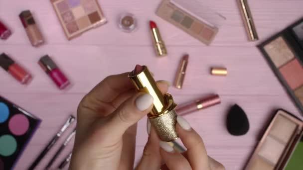 Žena otvírající rtěnku na růžovém plochém podkladu ležela na pozadí kolekce kosmetiky. Nástroje v kosmetickém průmyslu - palety na oči, ruměnec, lesk.