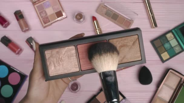 Žena pracující s obličejovou konturovací paletou na růžovém plochém podkladu ležela na pozadí kolekce kosmetiky. Nástroje v kosmetickém průmyslu - rtěnky, oční stíny, lesky.