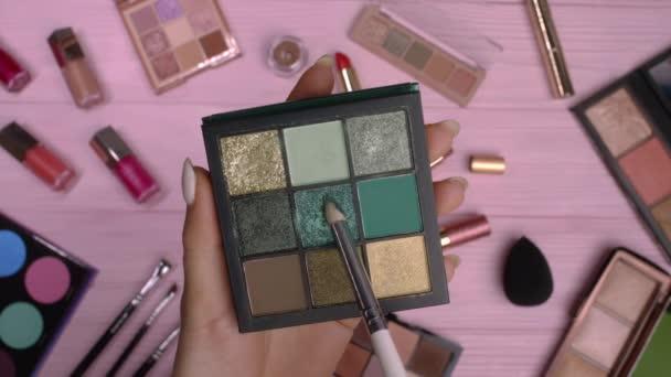 Žena pracující se zelenou oční paletou na růžovém plochém podkladu ležela na pozadí kolekce kosmetiky. Nástroje v kosmetickém průmyslu - rtěnky, rtěnky, lesky.
