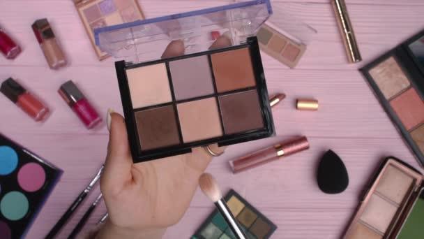 Žena pracující s oční paletou na růžovém plochém podkladu ležela na pozadí kolekce kosmetiky. Nástroje v kosmetickém průmyslu - rtěnky, rtěnky, lesky.