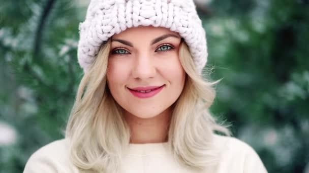 Vonzó szőke lány mosolyog, fehér kalapos hölgy. Portré fiatal csinos nő tökéletes smink és frizura az erdőben, téli szezonban.