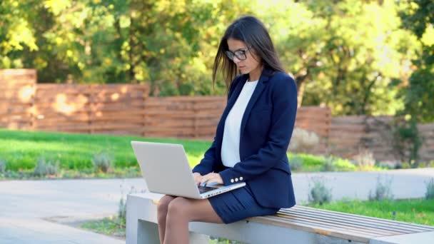 Sikeres üzletasszony laptoppal, zöld parki háttérrel. Gyönyörű lány formális kopás és szemüveg szörfözés internet vagy dolgozik az elektronikus eszköz
