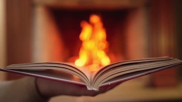 Lenyűgöző kilátás nyílik a nyitott könyv ellen égő tűz kandalló háttér. Papírirodalom, oktatási koncepció.