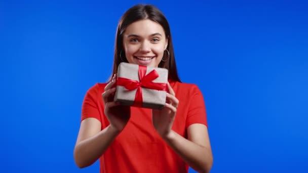Egy nő ajándékdobozzal a kezében, és kézzel adja oda a kék fal hátterű kamerának. Mosolygó lány, boldog a jelennel. Stúdió portré