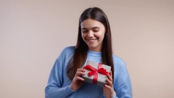 Izgatott nő kapott ajándék doboz íj. Boldog és hízeleg a figyelemnek. Lány mosolyog a jelen fény háttér. Stúdió portré