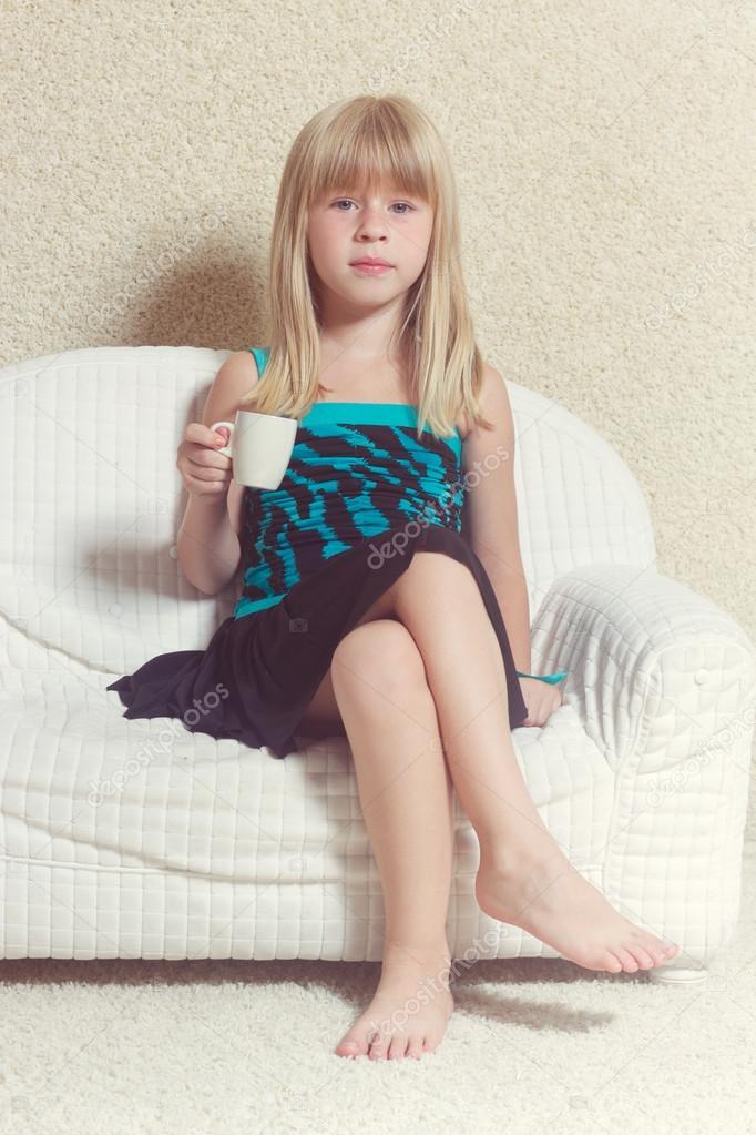 m dchen 5 jahre sitzen auf einem sofa mit tasse stockfoto victoshafoto 52159631. Black Bedroom Furniture Sets. Home Design Ideas