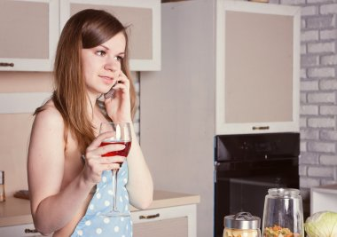 girl in the kitchen wearing an apron with a glass of  wine on  phone