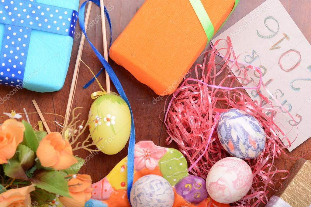 Easter with eggs in nest and yellow tulips over blue wooden table. Top view