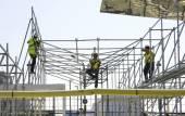 Fotografia Lavoratori durante la costruzione di un ponteggio
