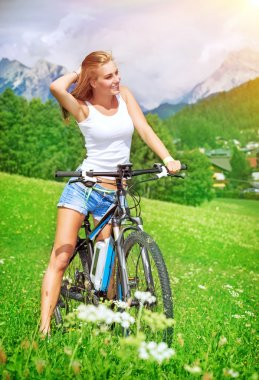 Happy fit woman on a bicycle traveling along mountainous village, healthy lifestyle, recreation in Alps, Austria, Europe stock vector