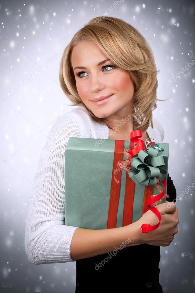 9a76b6b1c34f Πορτρέτο του χαριτωμένο ξανθιά γυναίκα με κιβώτιο δώρων στο χέρι την  χιονίζει φόντο