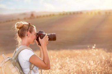 Happy traveler girl photographing ripe wheat field in bright sun rays, autumn harvest season, interesting profession, travel and tourism concept stock vector