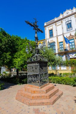 Wrought iron cross highly decorated in a park in Seville, Spain