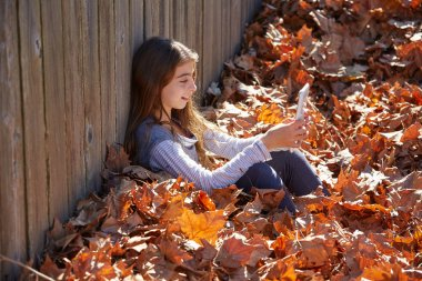 Kid girl playing tablet pc in autumn leaves