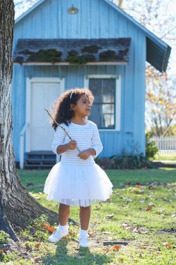 Kid girl with branch stick playing outdoor