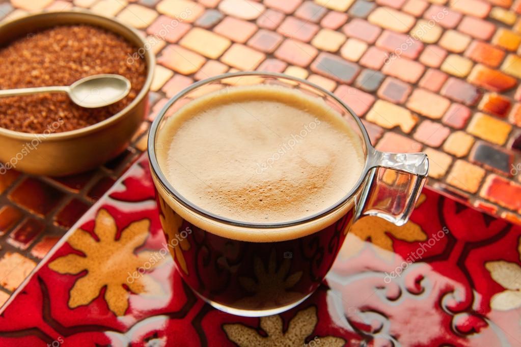 Tazza di vetro caffè con crema sul tavolo piastrelle rosso u foto
