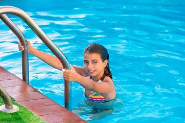 Kid girl in swimming pool at summer vacation