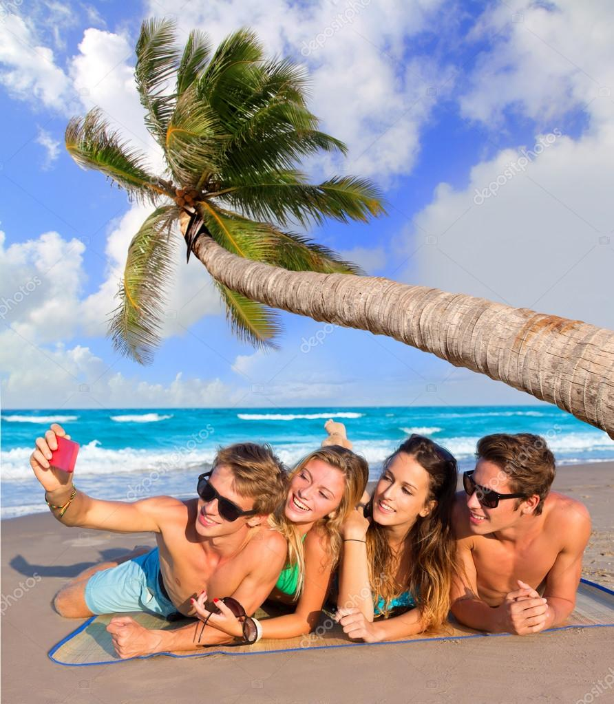 Selfie group of tourist friends in a tropical beach