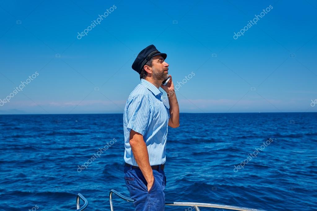 Captain cap sailor man talking mobile phone boat