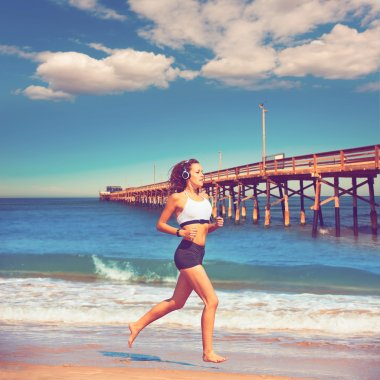 Beautiful brunette girl running in California beach