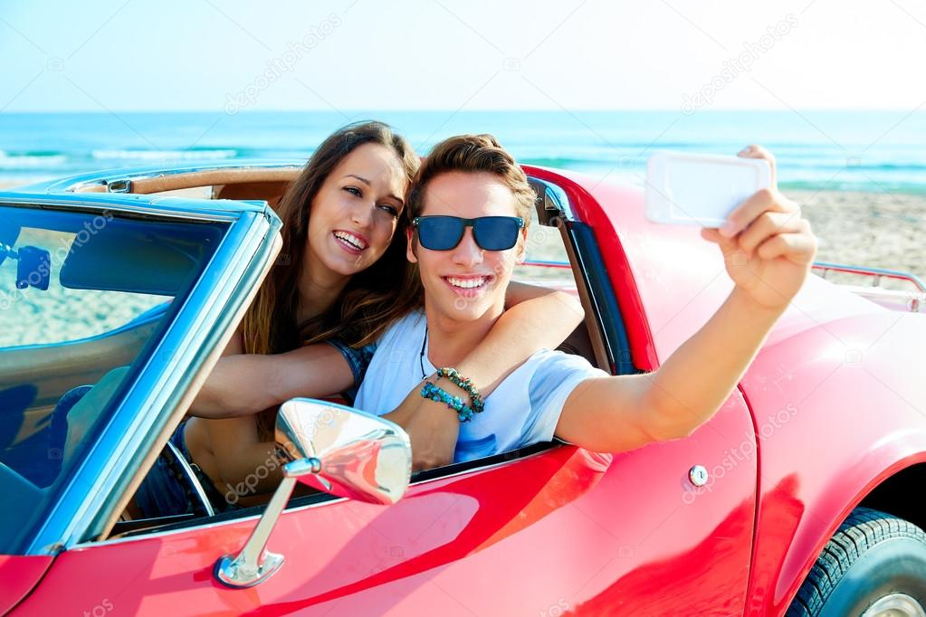 young couple selfie happy in res car on beach