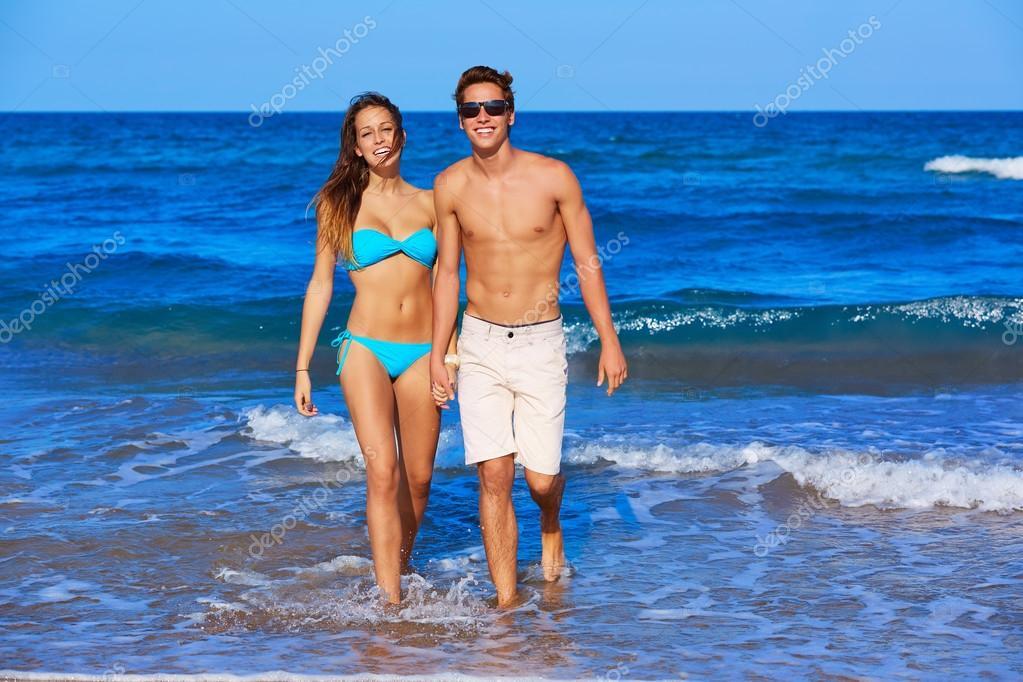 Beautiful young couple walking in the beach